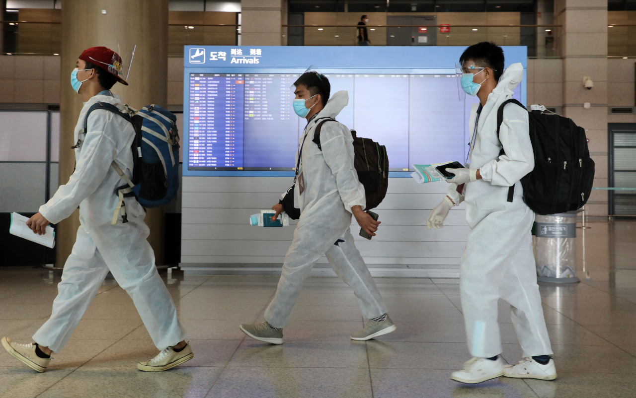 Foreigners in protective gear walk by an arrival dashboard at Incheon Airport on July 19. (Yonhap)