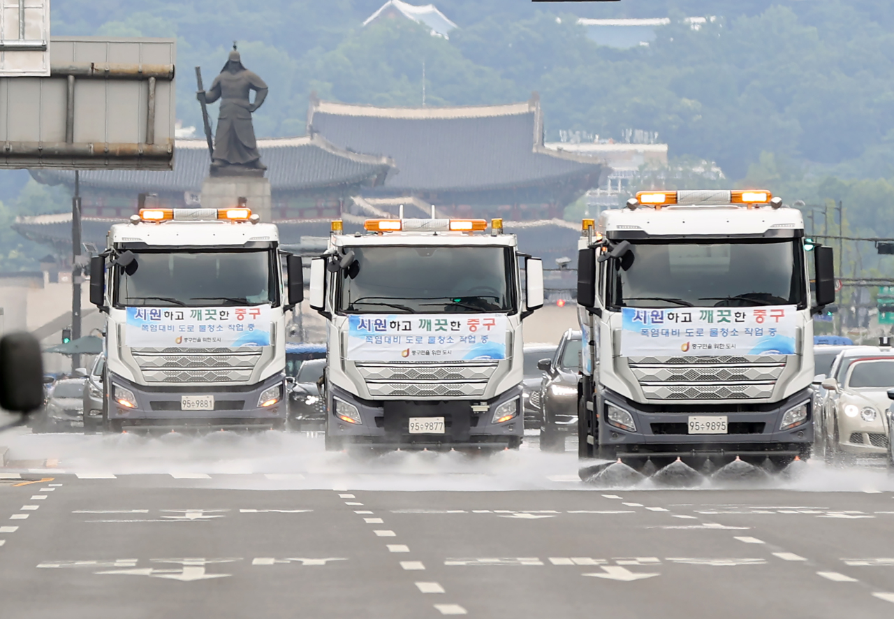 Trucks spray water onto the roads in Gwanghwamun, central Seoul, as temperatures rise to 33 degrees Celsius on Wednesday afternoon. (Yonhap)