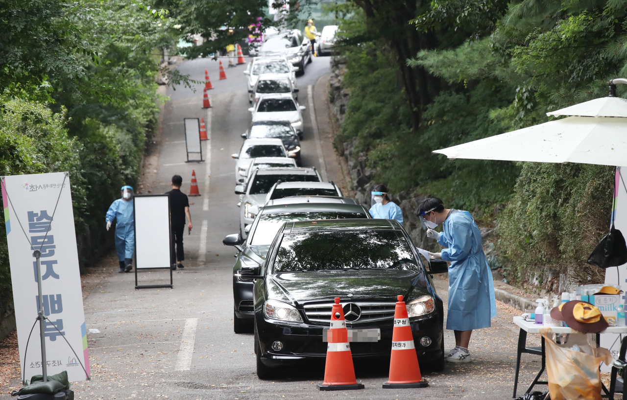 Cars wait in line to go through a drive-through COVID-19 testing station in Seoul on Thursday.(Yonhap)