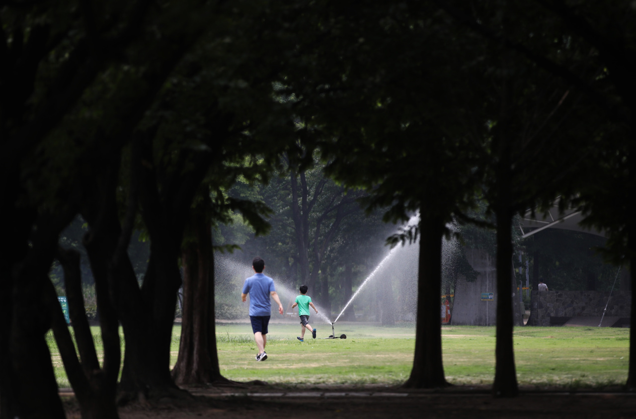 A man and a boy try to cool off around a sprinkler at a park in Seoul on Thursday. (Yonhap)