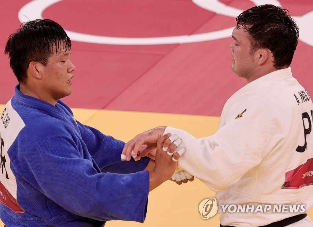Cho Guham of South Korea (L) holds the hands of Aaron Wolf of Japan after the final match of the men's 100kg judo contest in the Tokyo Olympics on July 29, 2021. (Yonhap)