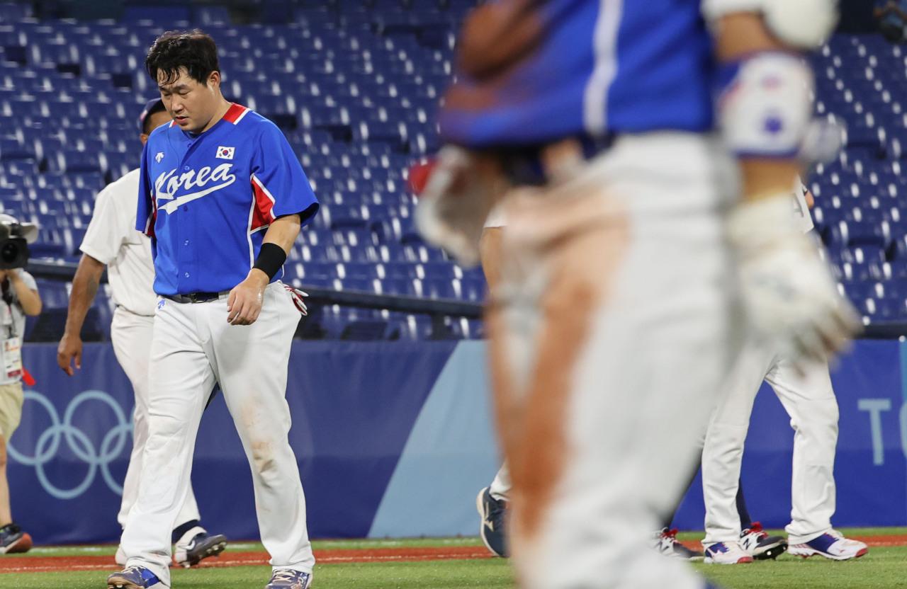 Yang Eui-ji of South Korea (L) walks off the field at Yokohama Stadium in Yokohama, Japan, after losing to the US 4-2 in their Group B game of the Tokyo Olympic baseball tournament on Saturday. (Yonhap)
