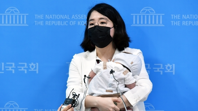 Rep. Yong Hye-in, 31, of the Basic Income Party, brings her 2-month-old son to her workplace on July 5. (Yonhap)