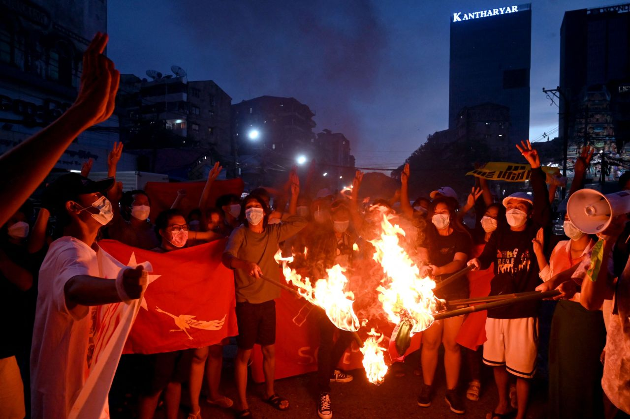 Protesters burn Myanmar flags during a demonstration against the military coup in Yangon on July 29. (AFP-Yonhap)
