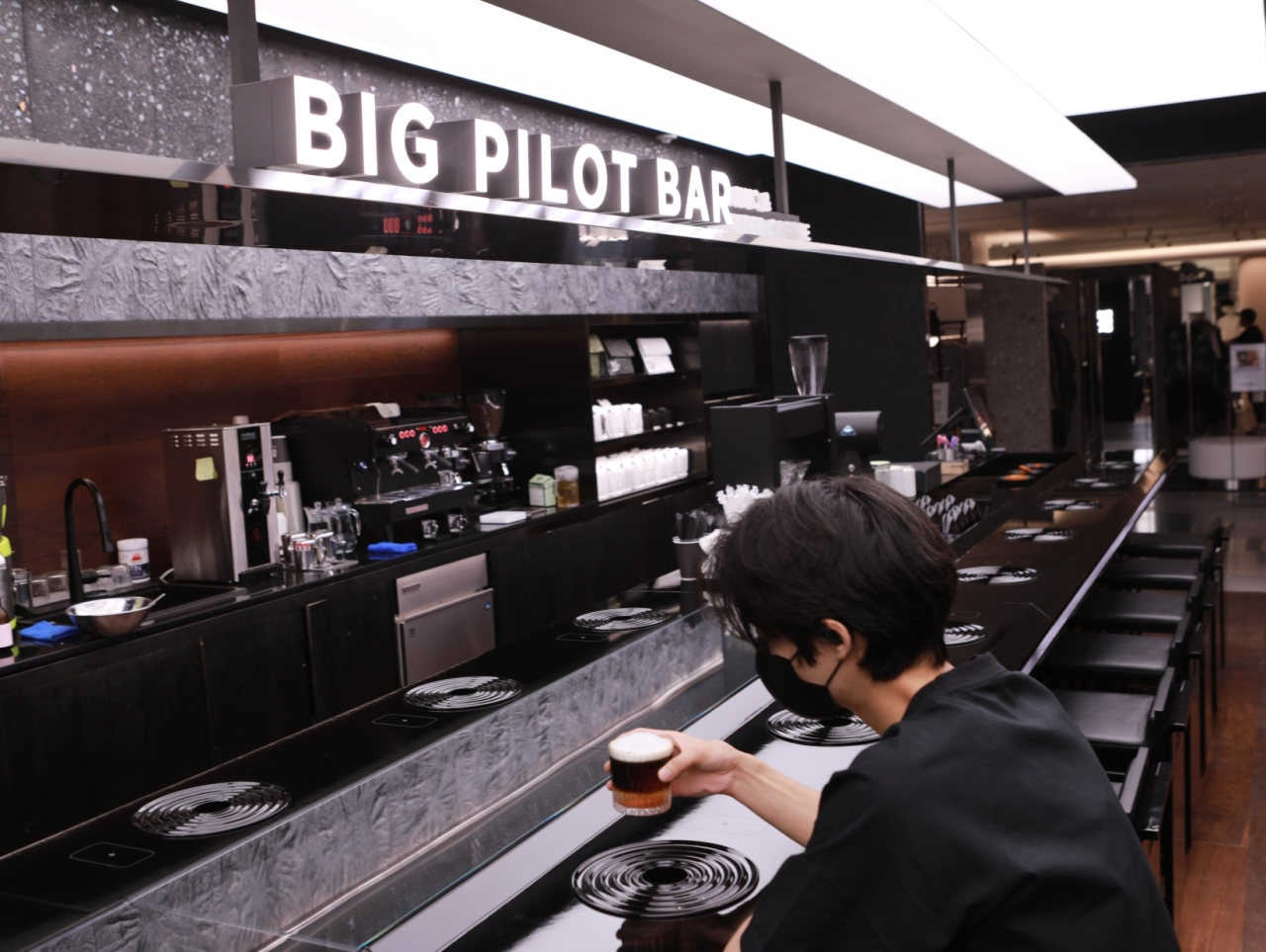A man drinks coffee at IWC's The Big Pilot Bar in Lotte Department Store's Euljiro flagship branch. (Lotte Shopping)