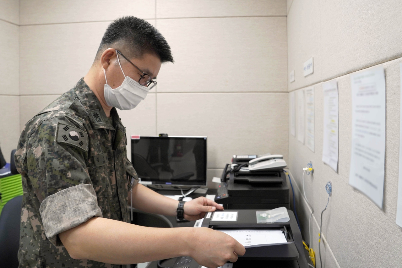 This photo, provided by the defense ministry on July 27, 2021, shows a South Korean service member sending a fax message to North Korea via the inter-Korean western military communication line. (defense ministry)