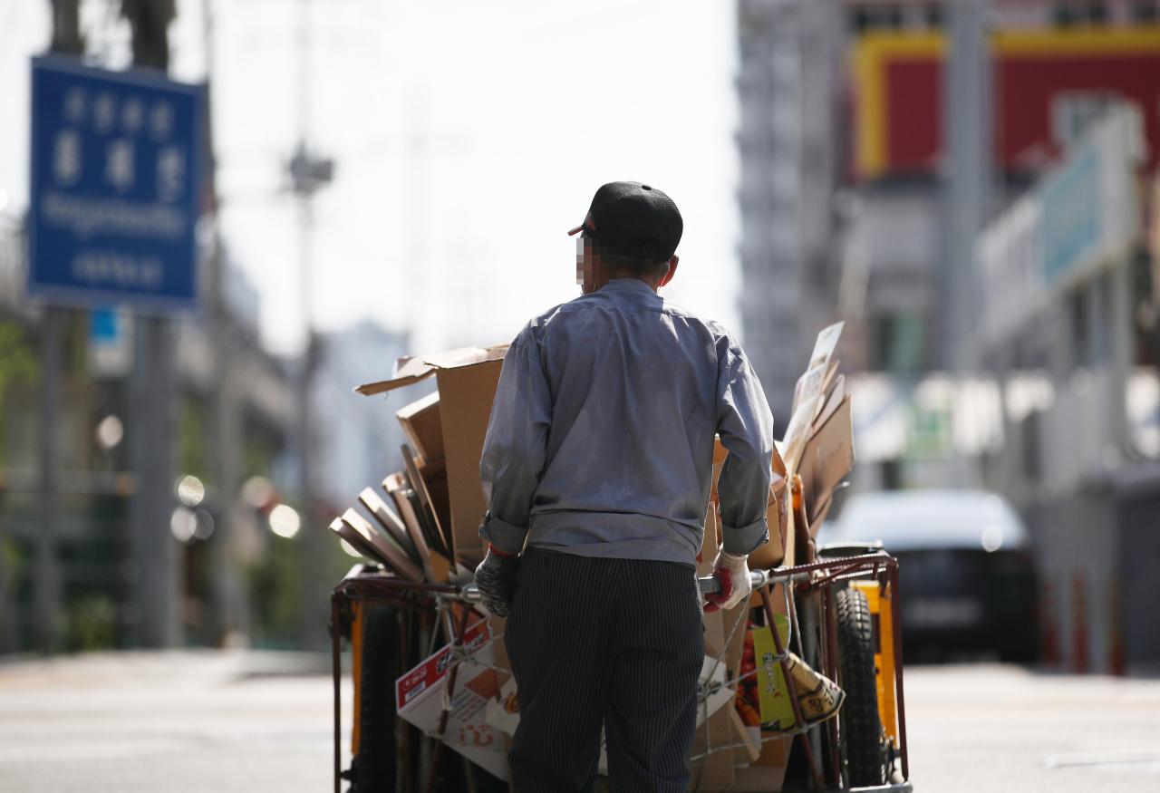 An elderly man pushes an overcrowded hand cart along a street near Hongjecheon in western Seoul on July 21. (Yonhap)