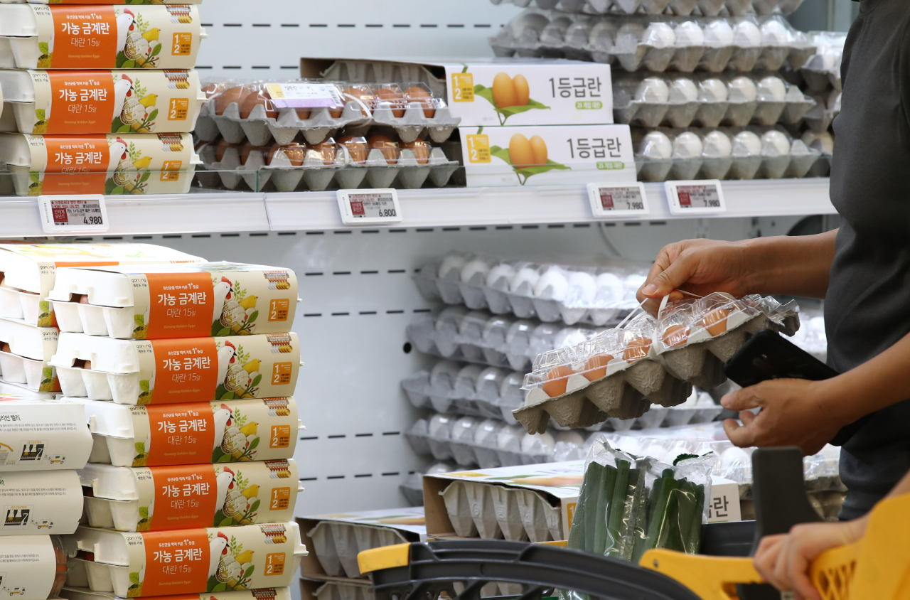 This file photo, taken July 27, 2021, shows a shopper selecting eggs at a discount store in Seoul. (Yonhap)