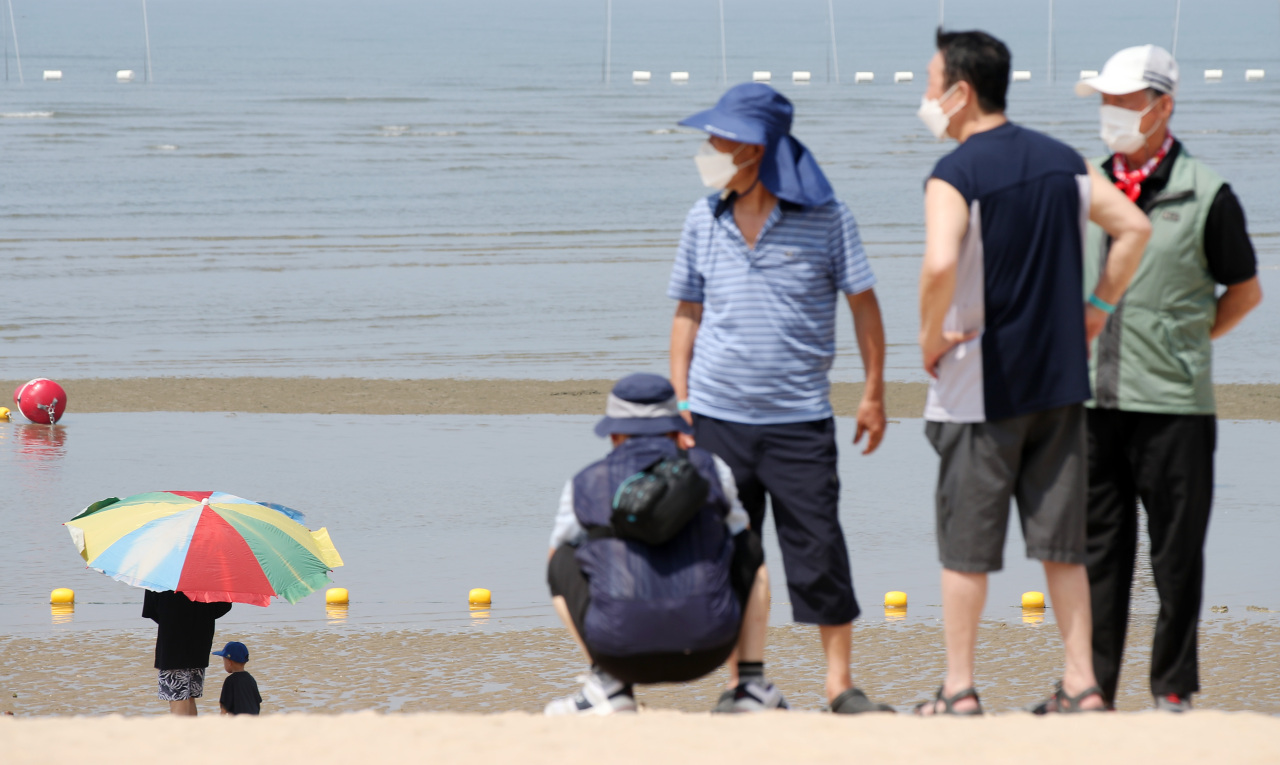Masked visitors walk along a beach in Incheon, west of Seoul, on Tuesday. (Yonhap)