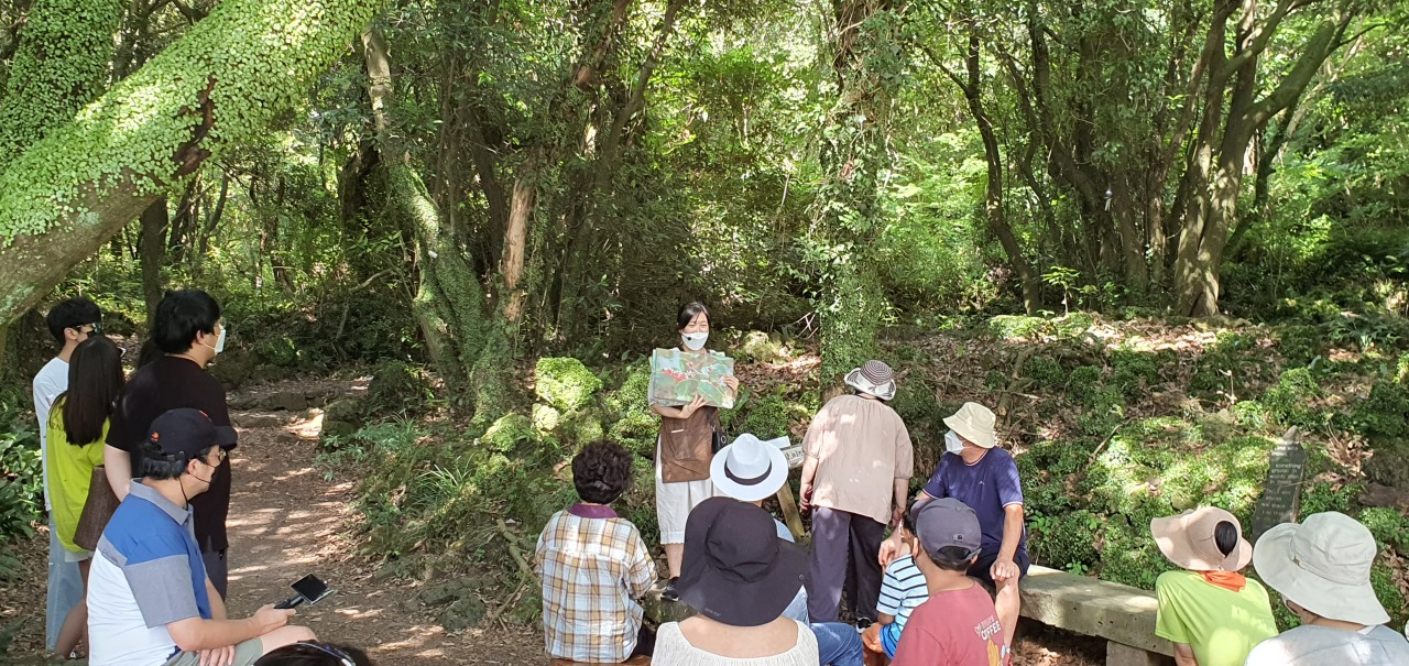 Forest reader Lee Ji-yeong explains the ecosystem of Gotjawal to visitors at Hwansang Forest Gotjawal Park on July 29. (Kim Hae-yeon/The Korea Herald)