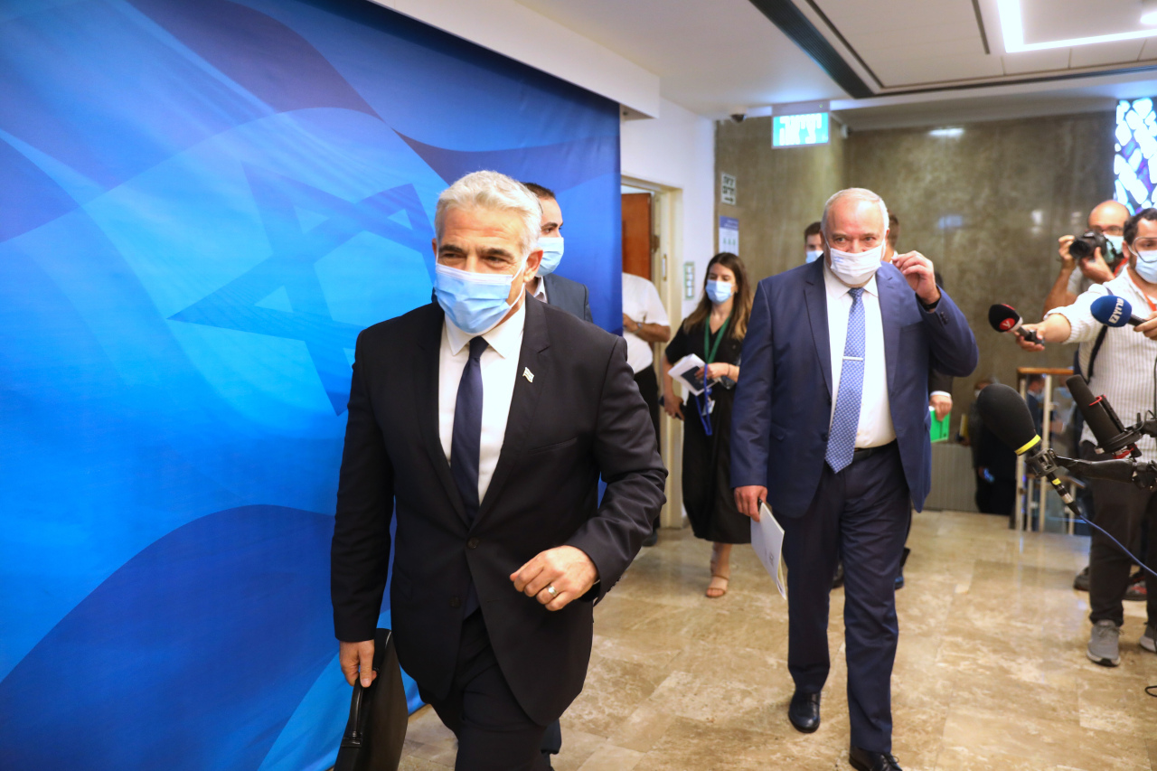 Israeli Foreign Minister Yair Lapid (left) and Fineness Minister Avigdor Lieberman attend a cabinet meeting at the prime minister's office in Jerusalem, Sunday. (AP-Yonhap)