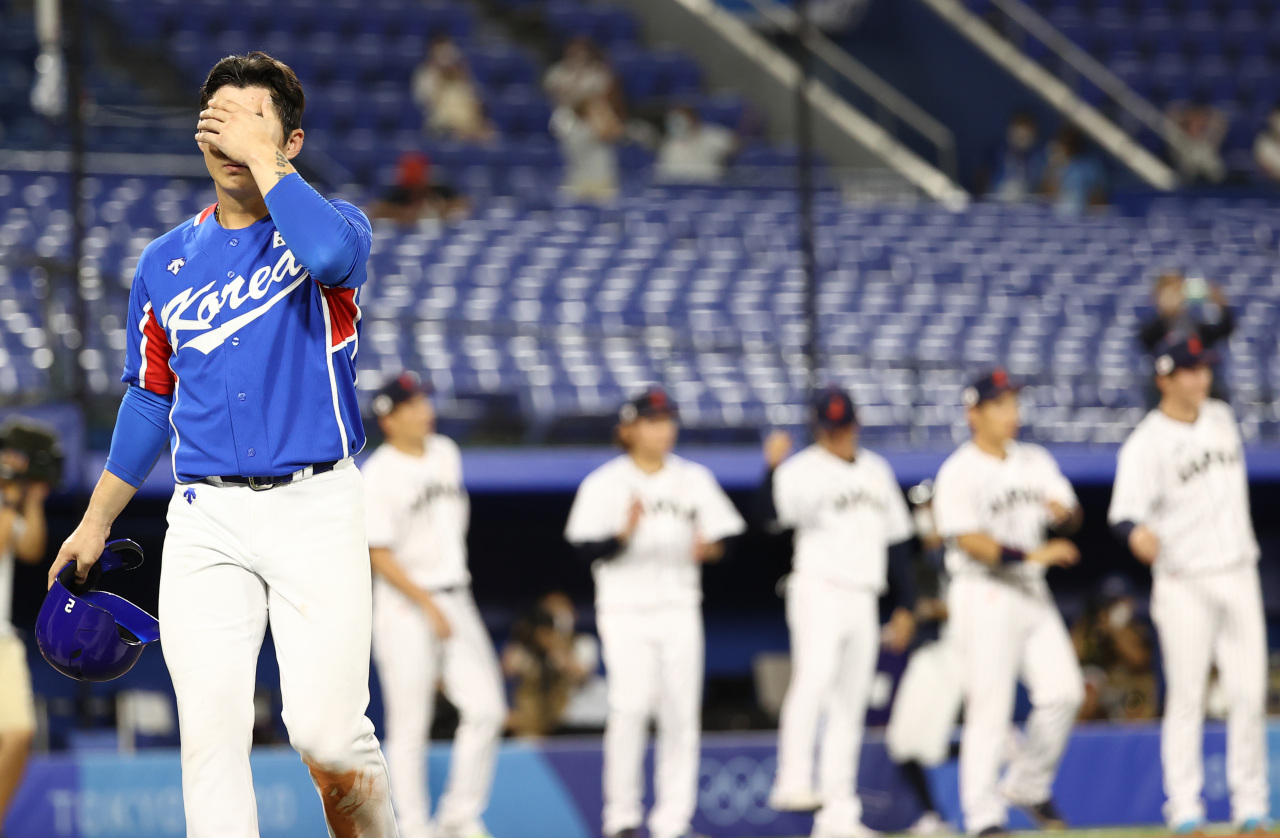 South Korean national baseball team shortstop Oh Ji-hwan (left) covers his face with his left hand as Korea conceded in a semifinal against Japan Wednesday. (Yonhap)