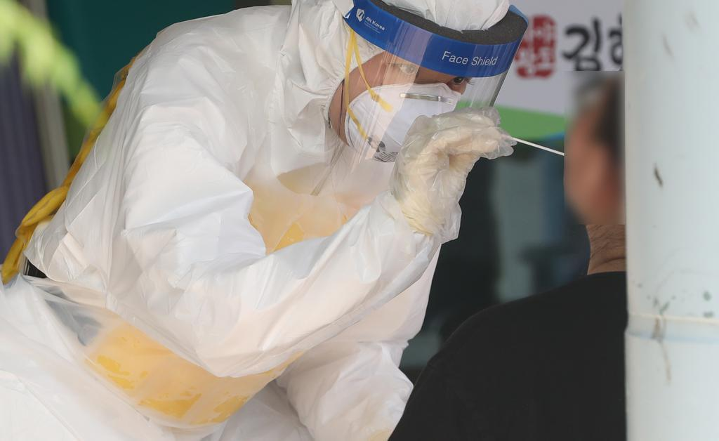 A health worker in a protective suit collects a sample from a citizen at a virus testing clinic in Gimhae, South Gyeongsang Province, on Wednesday. (Yonhap)
