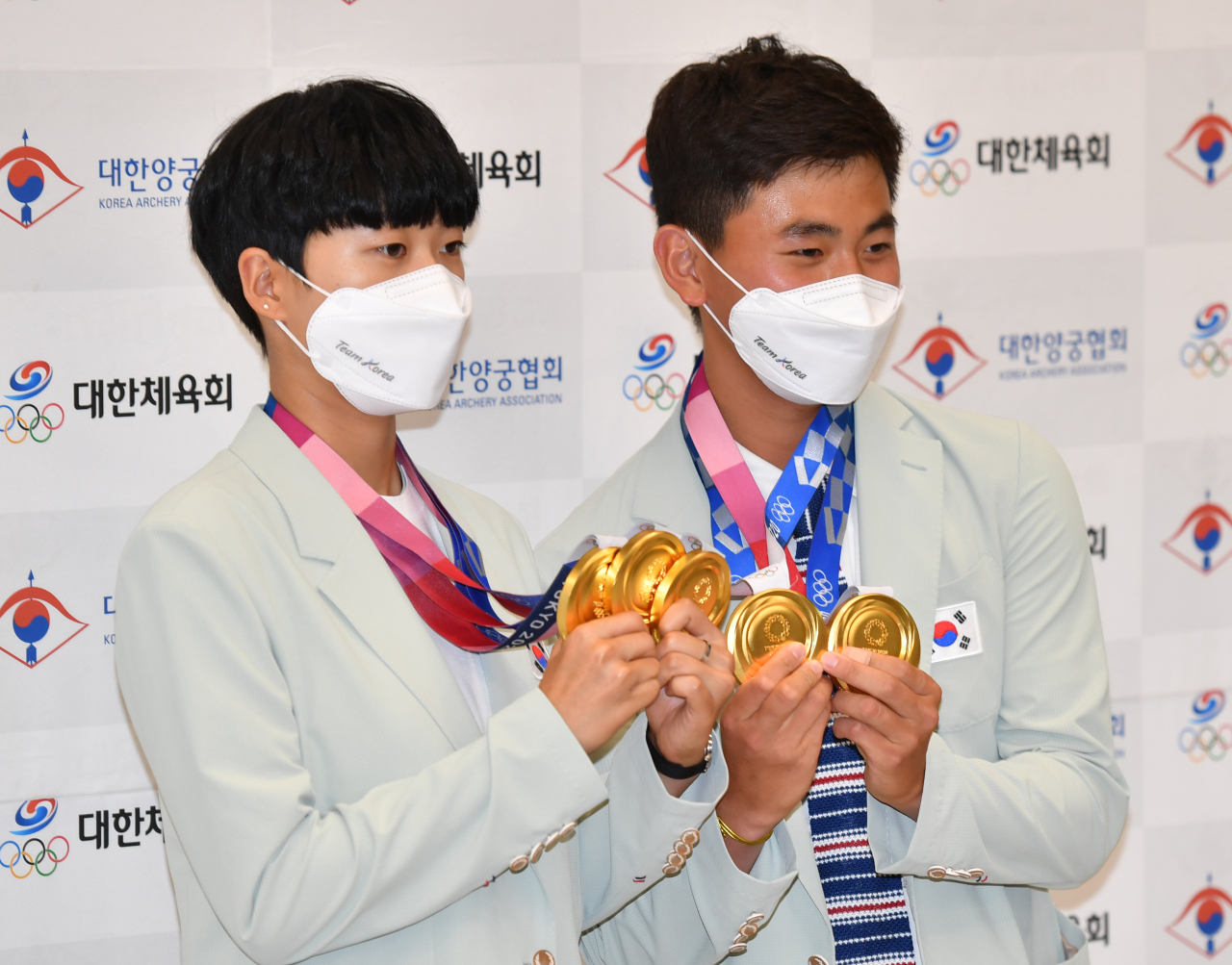 Archery gold medalists An San (left) and Kim Je-deok pose for a photo at Incheon Airport on Sunday. (Yonhap)