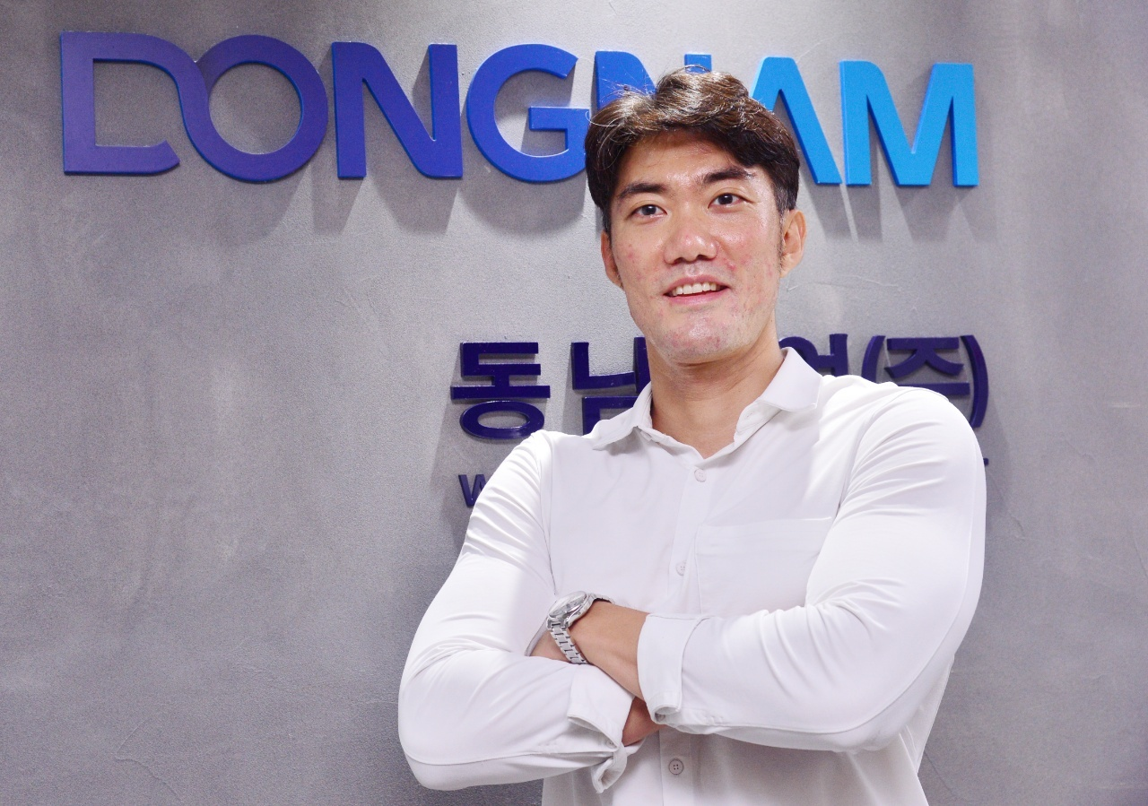Dongnam Construction Chemical CEO poses in front of the company logo, at its office in Pangyo, Gyeonggi Province, Wednesday. (Park Hyun-koo/The Korea Herald)