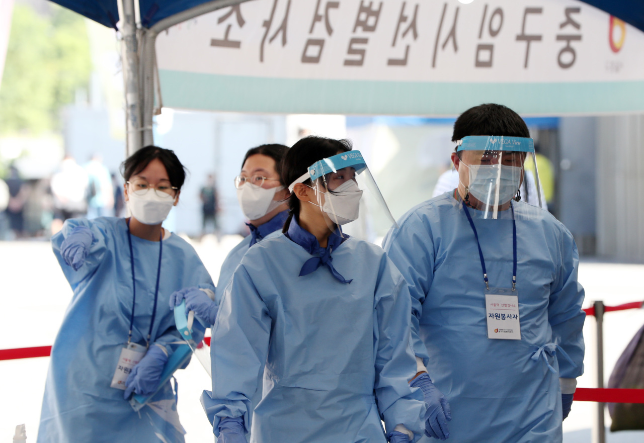Photo shows health workers in protective suits at a Seoul testing center as temperatures rise past 30 degrees Celsius on Thursday. (Yonhap)