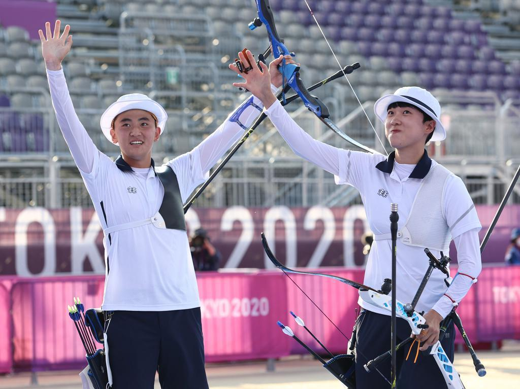 South Korean archers Kim Je-deok (L) and An San celebrate after clinching the gold medal in the mixed team event at the Tokyo Olympics at Yumenoshima Park Archery Field in Tokyo on July 24, 2021. (Yonhap)