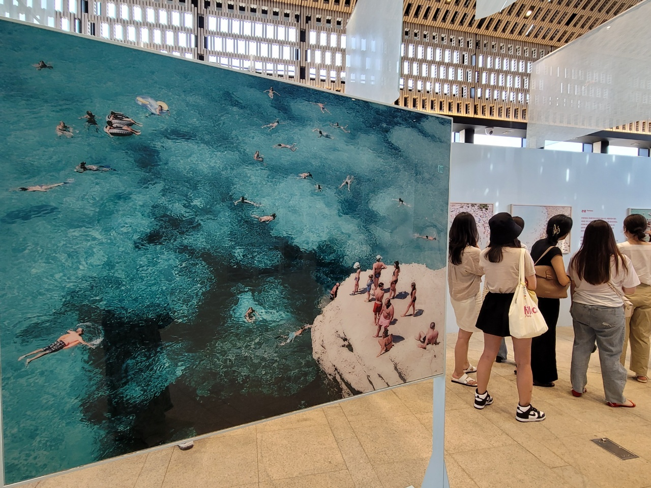 """Visitors view works on display at """"Photographs by Yosigo: Holiday Memories"""" at Ground Seesaw Seochon in Seoul on Thursday. (Park Yuna/The Korea Herald)"""