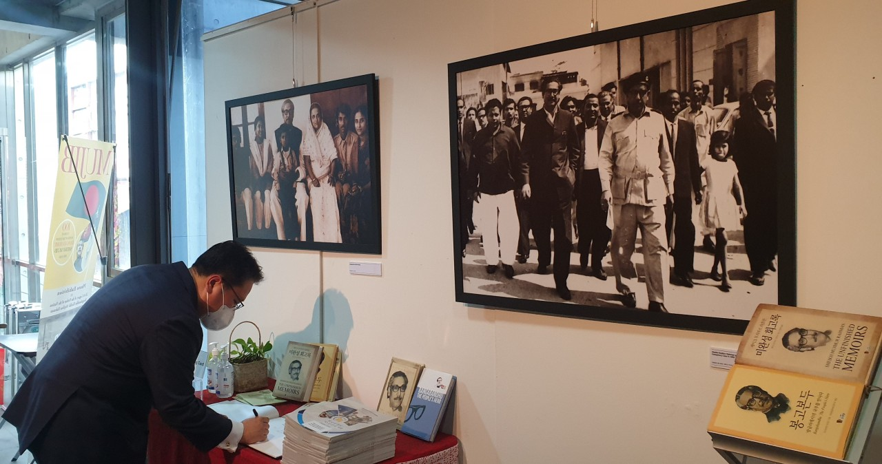 A visitor signs the guest book at a photo exhibition celebrating the life and legacy of Bangladesh's national hero, Sheikh Mujibur Rahman, known as Bangabandhu, last week at a cultural center in Seoul. (Embassy of Bangladesh in Seoul)