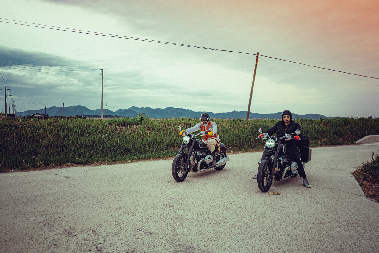 Comedian Ro Hong-chul (left) and singer Rain pose with their motorbikes. (Netflix)