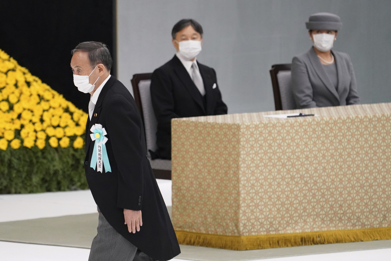Japanese Prime Minister Yoshihide Suga walks past Japan's Emperor Naruhito and Empress Masako to deliver a speech during a ceremony to mark the 76th anniversary of Japan's surrender in World War II at Budokan hall in Tokyo Sunday. (AP-POOL Bloomberg-Yonhap)