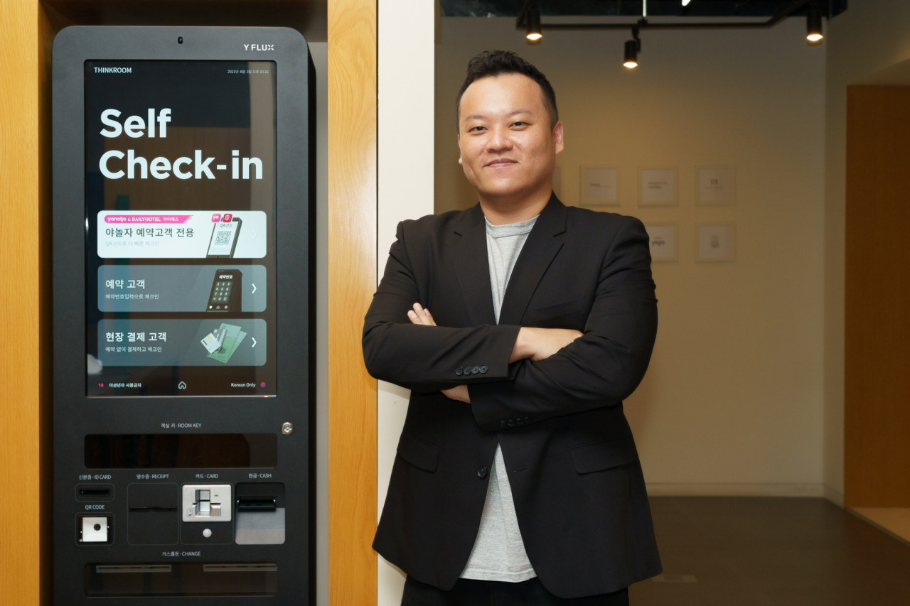 Lee Sang-jin, director of solution business at Yanolja Cloud, stands next to a Y Flux self check-in kiosk (Yanolja)
