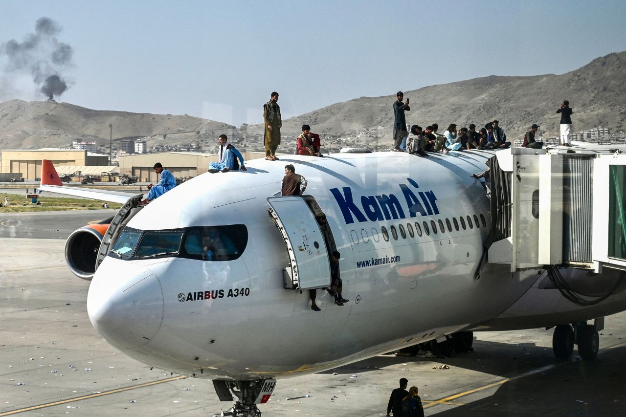 Afghan people climb atop a plane as they wait at the airport in Kabul on Monday, after a stunningly swift end to Afghanistan's 20-year war. (AFP-Yonhap)