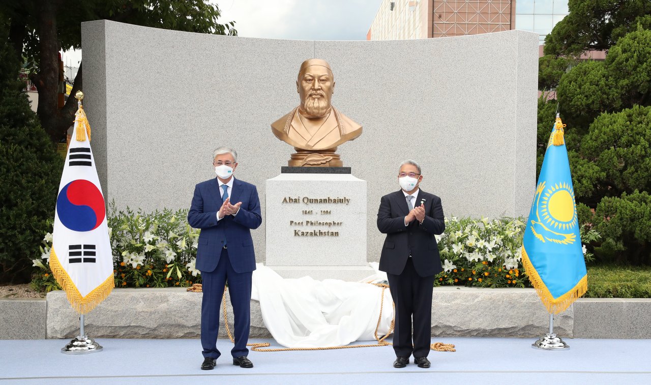 Kazakhstan President Kassym-Jomart Tokayev (left) and Lee Sang-kyun, chair of the Shinil Education Foundation, clap during a ceremony to unveil the statue of Abai Qunanbaiuly at Seoul Cyber University in Seoul on Tuesday. (Seoul Cyber University)
