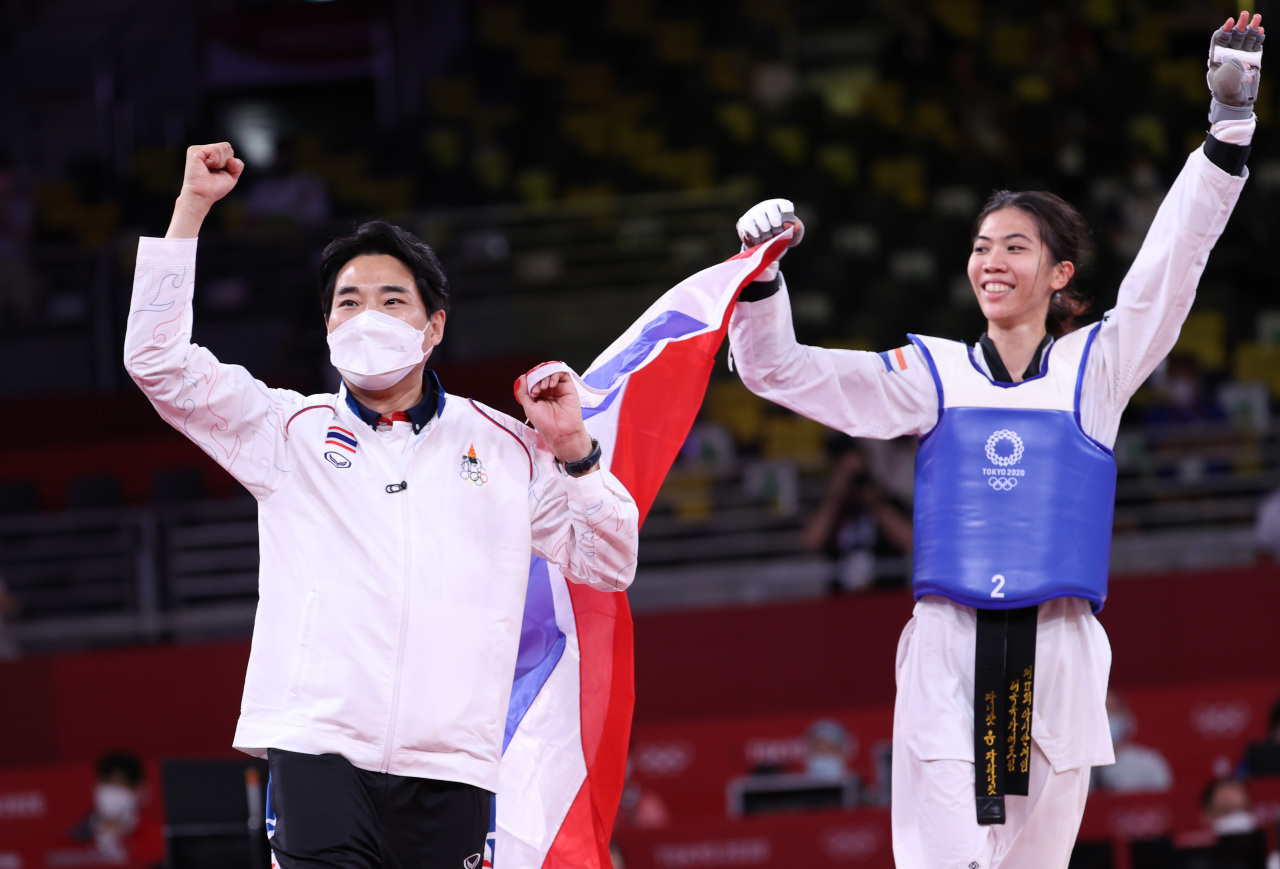 Choi Young-seok (L), the South Korean-born coach of the Thai taekwondo team, and his athlete Panipak Wongpattanakit celebrate Wongpattanakit's gold medal in the women's 49kg class at the Tokyo Olympics at Makuhari Messe Hall A in Chiba, Japan, on July 24, 2021. (Yonhap)