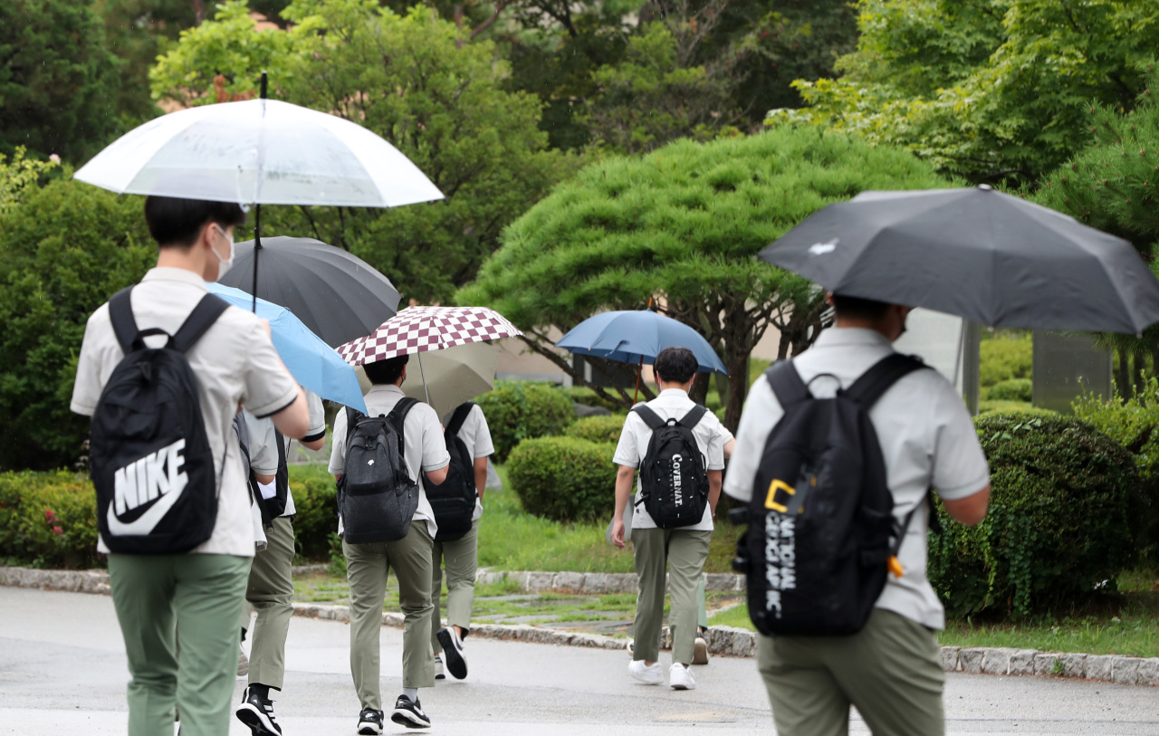 Photo shows students withing umbrellas in the rain at a high school in Chuncheon, Gangwon Province. (Yonhap)