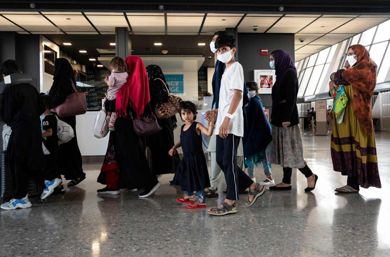 Refugees from Afghanistan are escorted to a waiting bus after arriving and being processed at Dulles International Airport in Dulles, Virginia on Monday. (AFP-Yonhap)