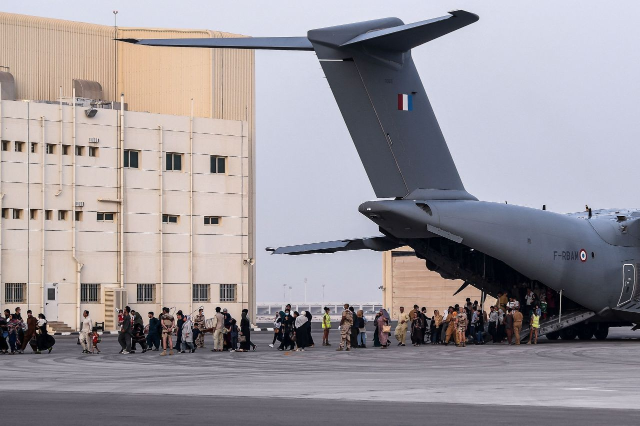 This AFP photo by Bertrand Guay shows Afghan people walking on the tarmac as they disembark from an Airbus A400M military transport aircraft at the French military air base 104 of Al Dhafra, near Abu Dhabi, on Monday, after being evacuated from Kabul as part of Operation Apagan. (AFP-Yonhap)