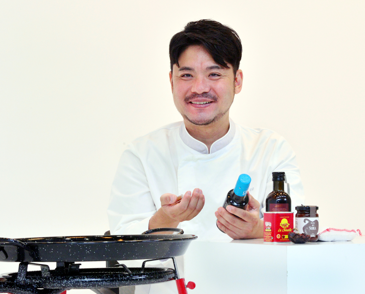 Lee Sang-hoon shows basic paella ingredients during an interview at The Korea Herald's studio in Seoul on Monday. (Park Hyun-koo / The Korea Herald)