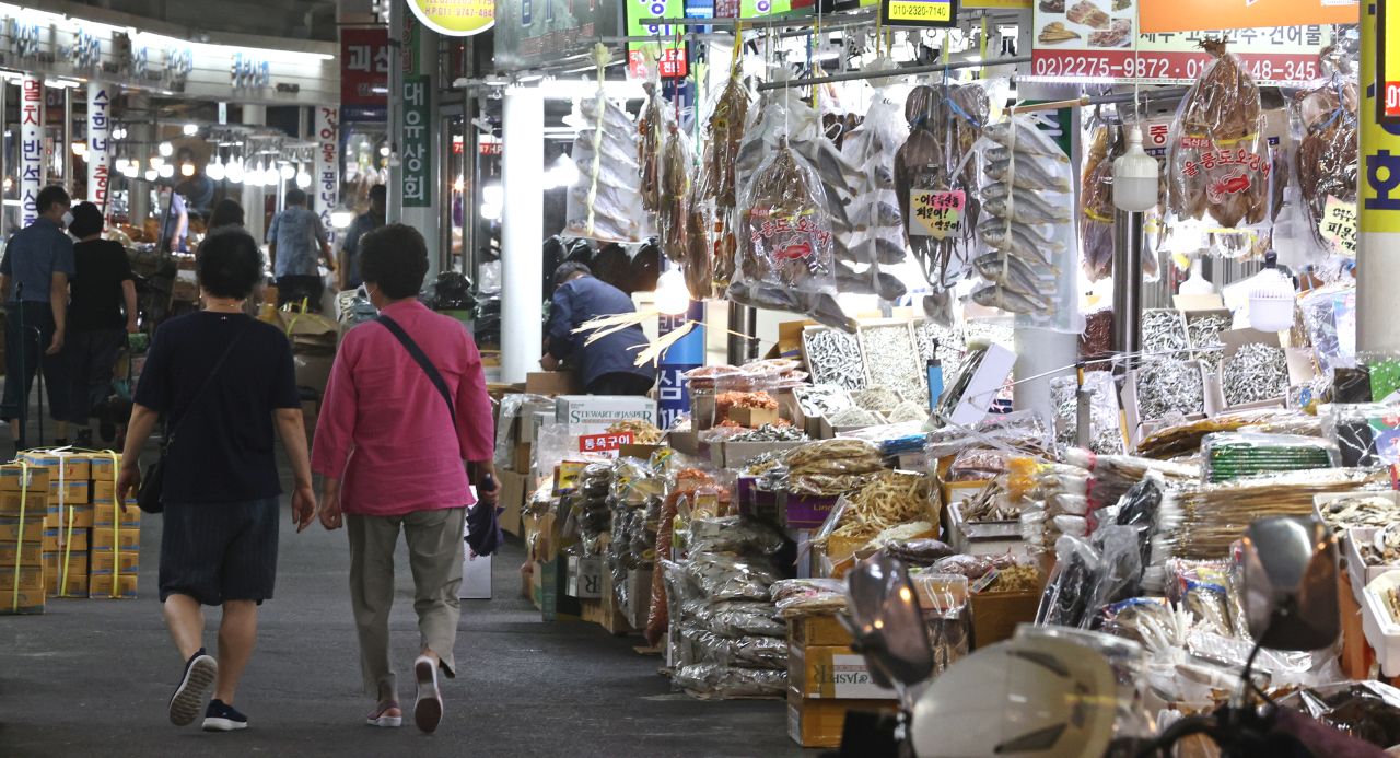 Customers shop for groceries at Jungbu Market in Seoul, on Thursday. (Yonhap)