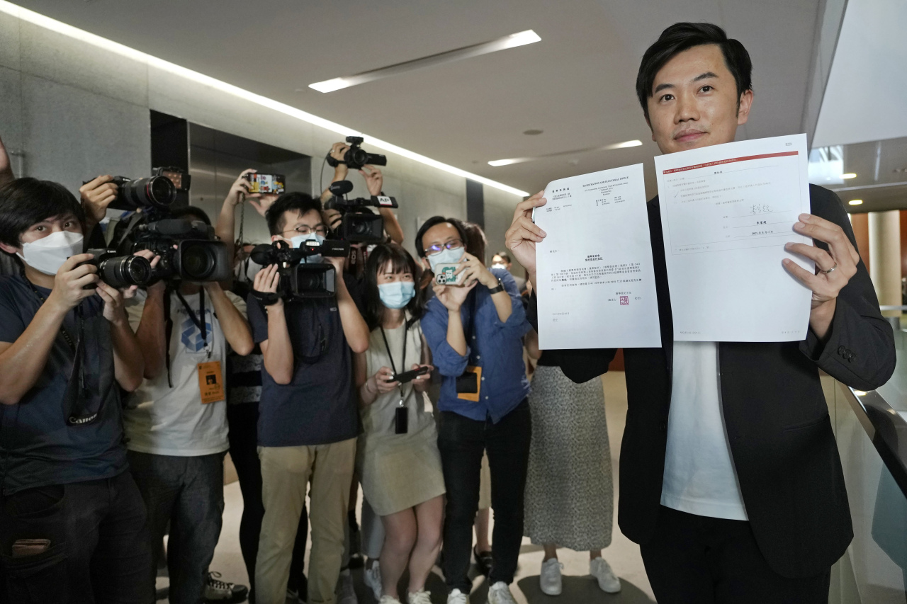Lawmaker Chung-Tai Cheng displays a document as he is surrounded by reporters after being disqualified from the legislature in Hong Kong on Thursday. (Yonhap-AP)