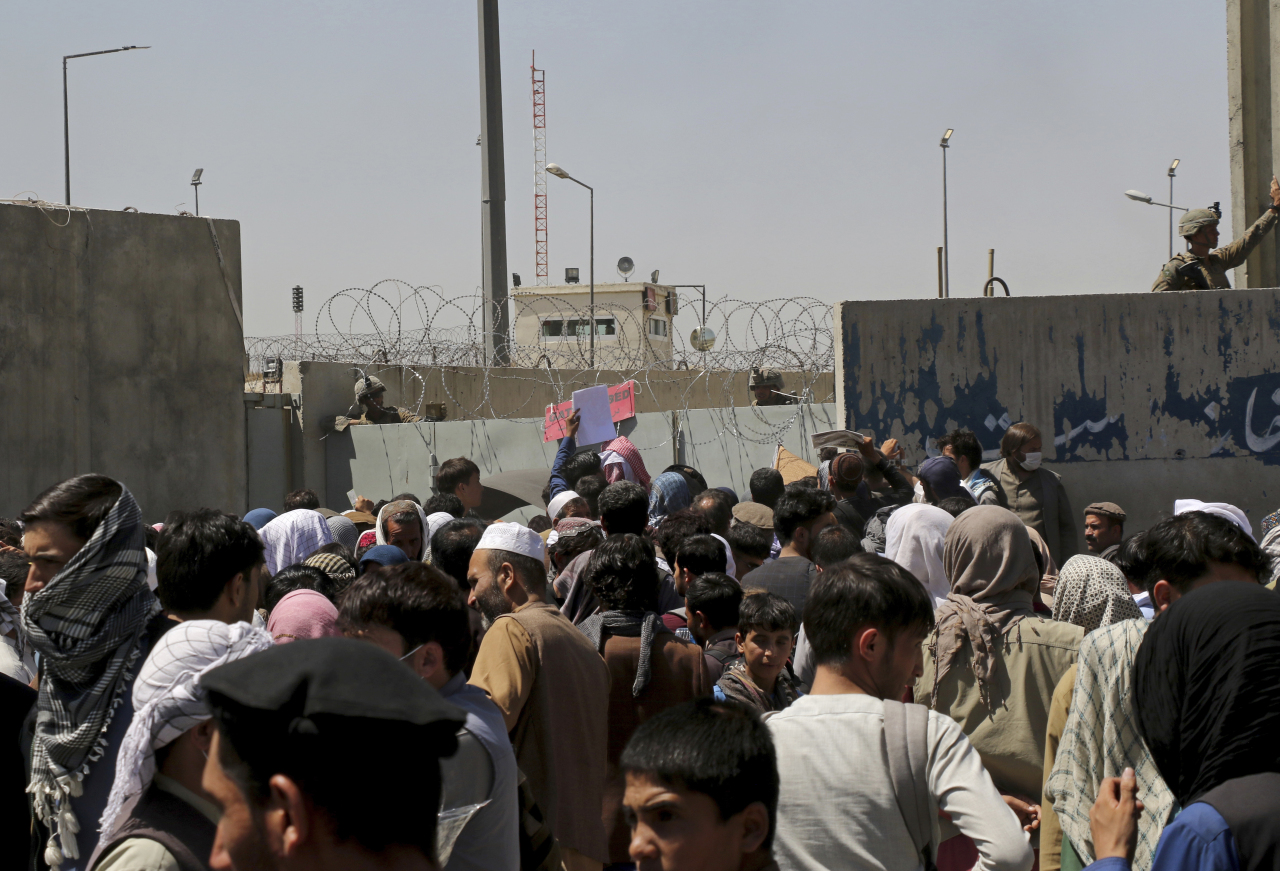 US soldiers stand inside the airport wall as hundreds of people gather near an evacuation control checkpoint on the perimeter of the Hamid Karzai International Airport, in Kabul, Afghanistan on Thursday. (Yonhap-AP)