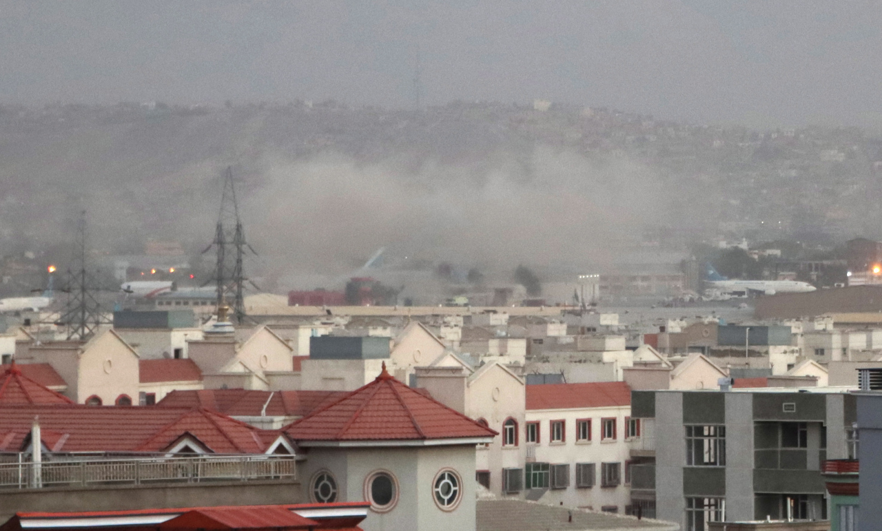 This EPA photo shows smoke billowing from the airport area after a blast outside the Hamid Karzai International Airport, in Kabul, Afghanistan, on Thursday. (EPA-Yonhap)
