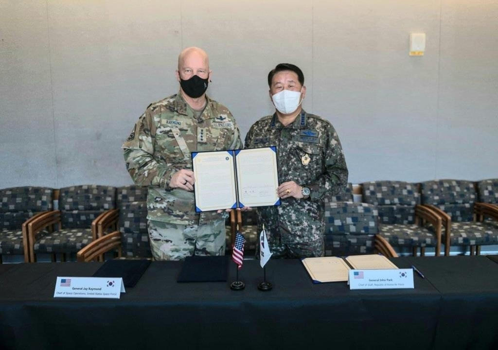 Air Force Chief of Staff Gen. Park In-ho (R) and US chief of space operations, Gen. John Raymond, sign a memorandum of understanding on forming a joint space policy consultative body at the Air Force Space Command in Colorado, US, on Friday (local time), in this photo provided by South Korea's Air Force on Sunday.(Yonhap)