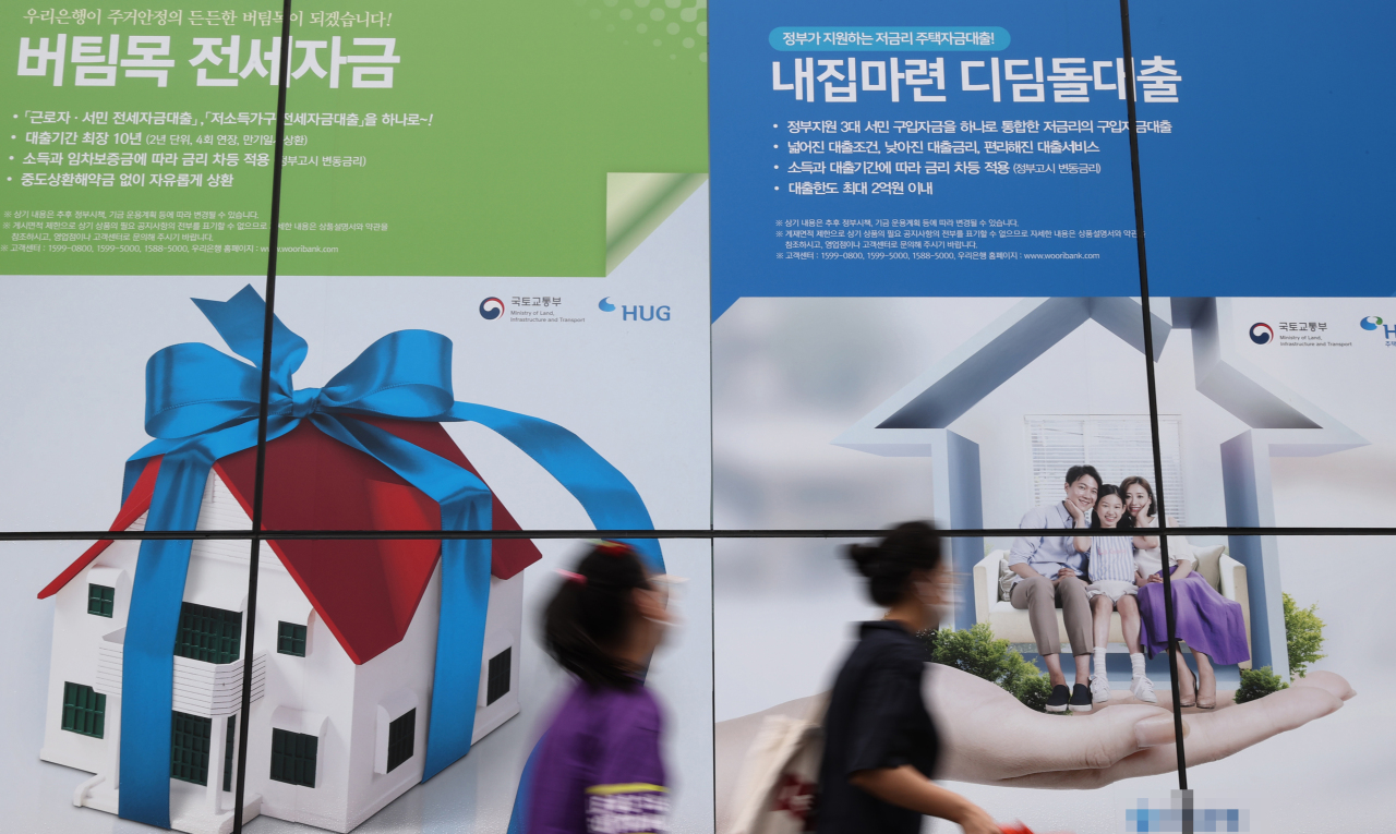 People walk past a poster advertising a commercial bank`s mortgages in Seoul. (Yonhap)