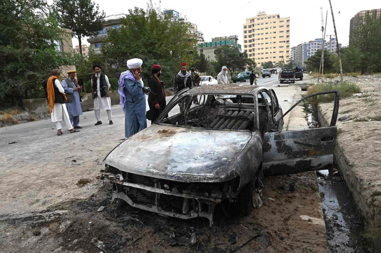 Taliban fighters investigate a damaged car after multiple rockets were fired in Kabul on Monday. Rockets flew across the Afghan capital on Monday as the US raced to complete its withdrawal from Afghanistan, with the evacuation of civilians all but over and terror attack fears high. (AFP-Yonhap)
