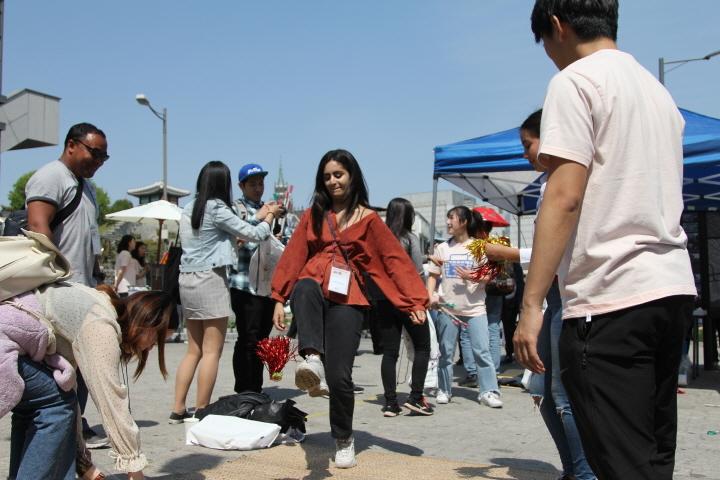 "Foreigners play ""jegichagi,"" a Korean traditional folk game, at Nammun Market in Suwon, Gyeonggi Province, in May 2019. (Korea Tourism Organization)"
