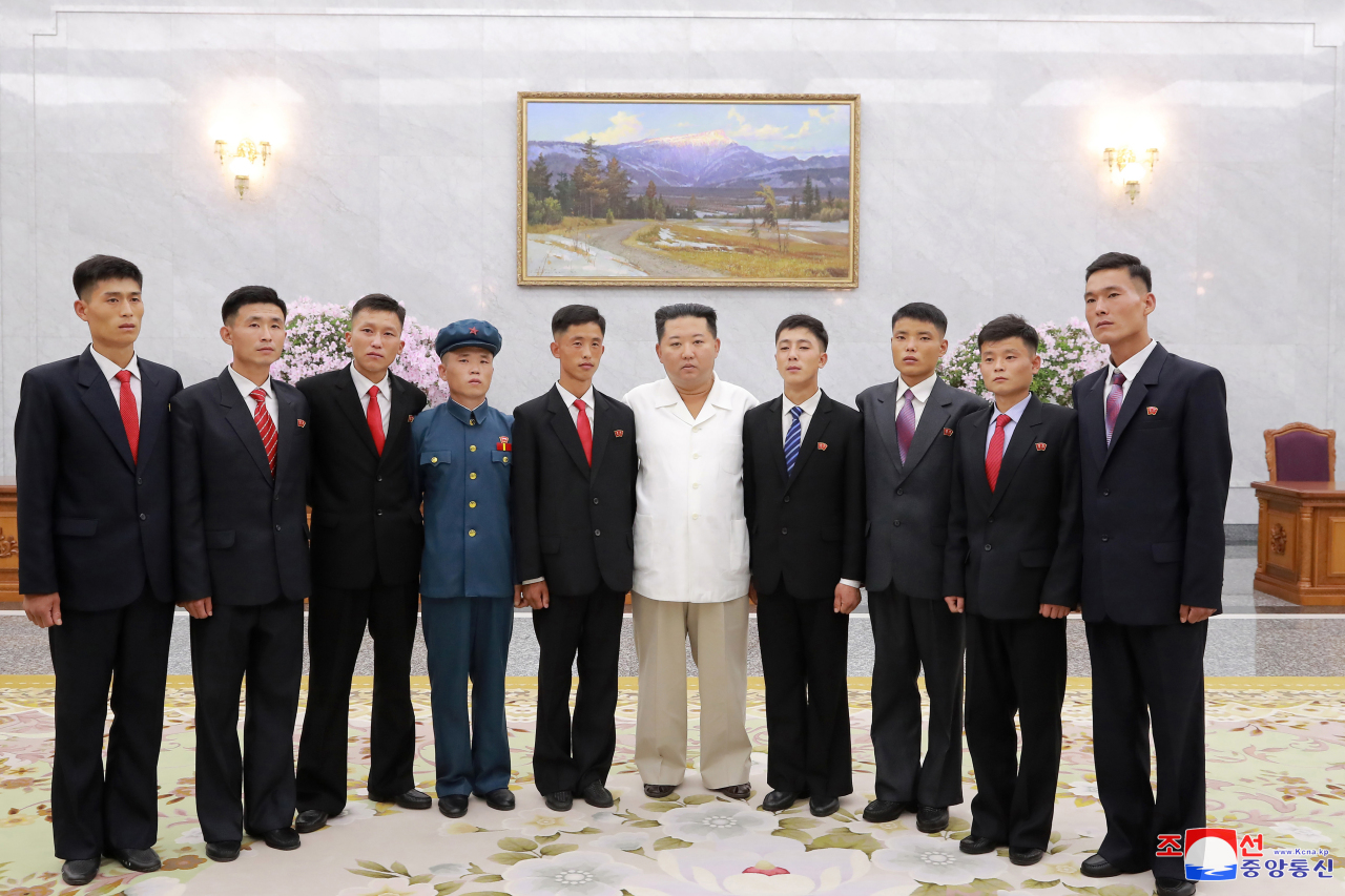 North Korean leader Kim Jong-un holds a photo session with young ex-convicts who volunteered to work in