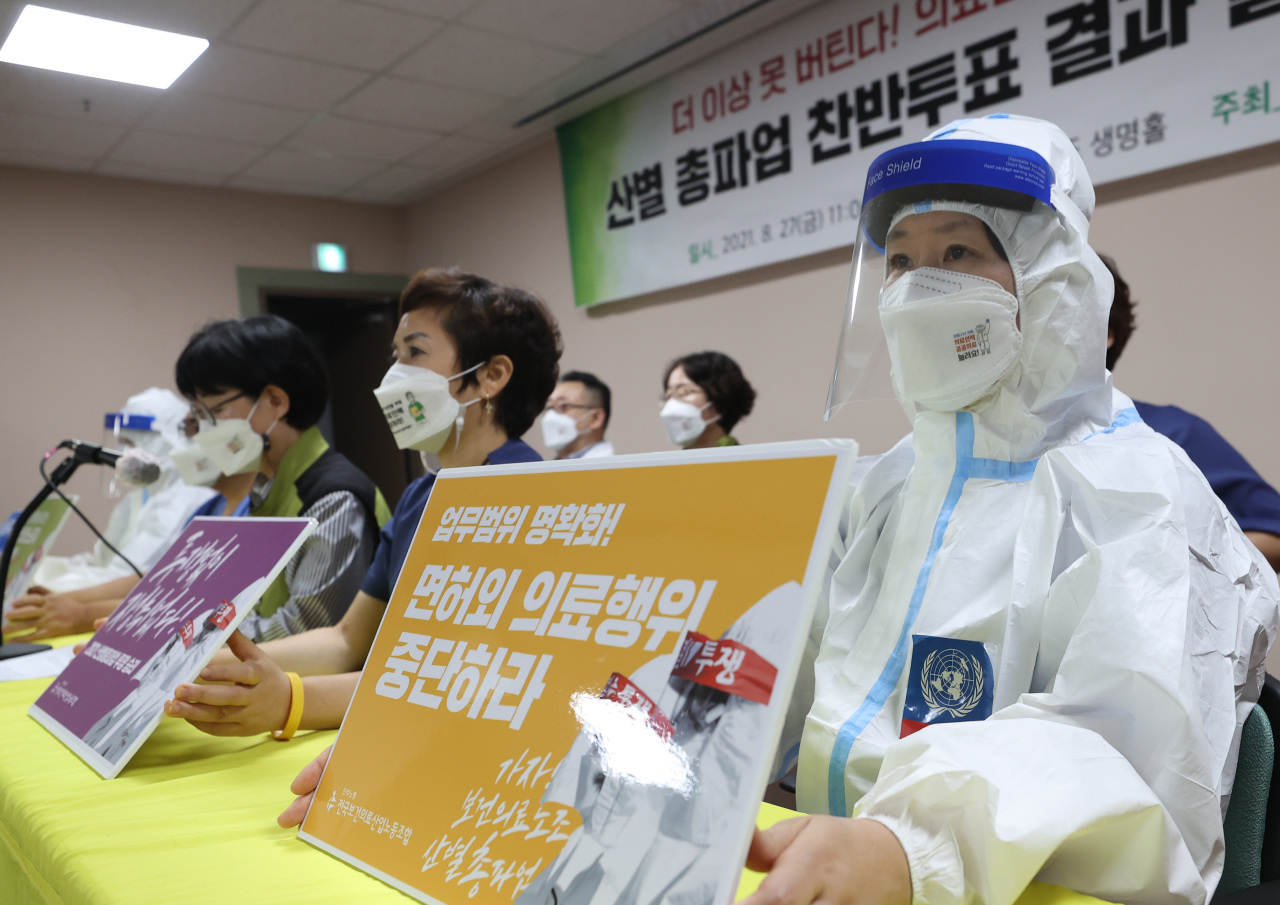 Members of the Korea Health and Medical Workers' Union hold a press conference in western Seoul on Friday, after voting to go on strike beginning Sept. 2 to demand improved working conditions. (Yonhap)