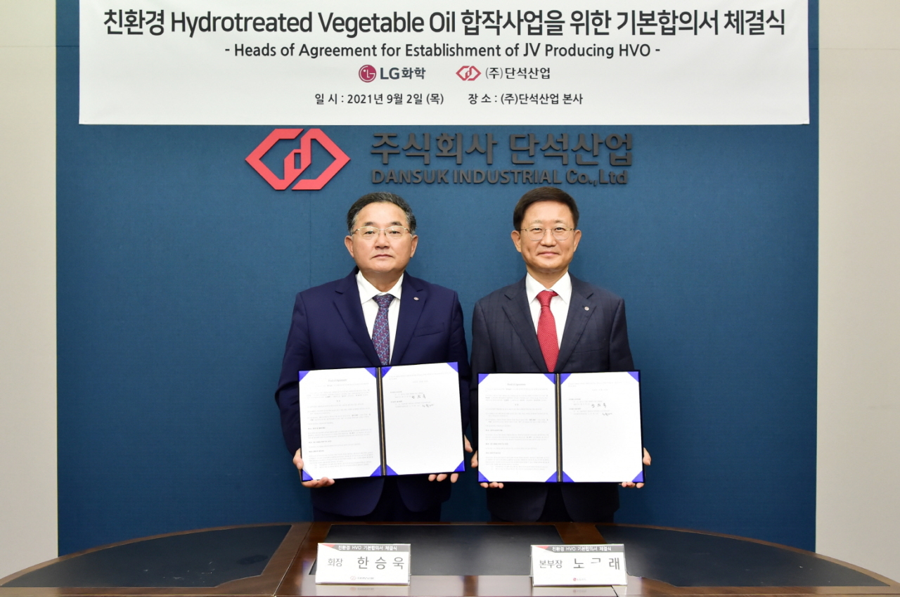 Noh Kug-lae, president of LG Chem's petrochemical operations (right) and Han Seung-uk, chairman of Dansuk Industrial, pose after signing a head of agreement at Dansuk Industrial headquarters in Siheung, Gyeonggi Province, Thursday. The two agreed to form a joint venture and build South Korea's first hydrogen-treated vegetable oil factory in Daesan petrochemical complex in South Chungcheong Province. (LG Chem)