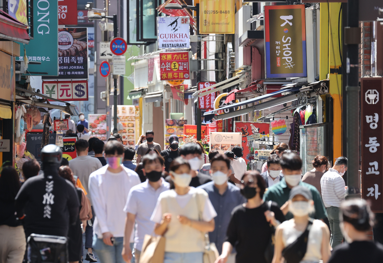 People walk in the streets of Myeong-dong in central Seoul during lunchtime on Friday. (Yonhap)
