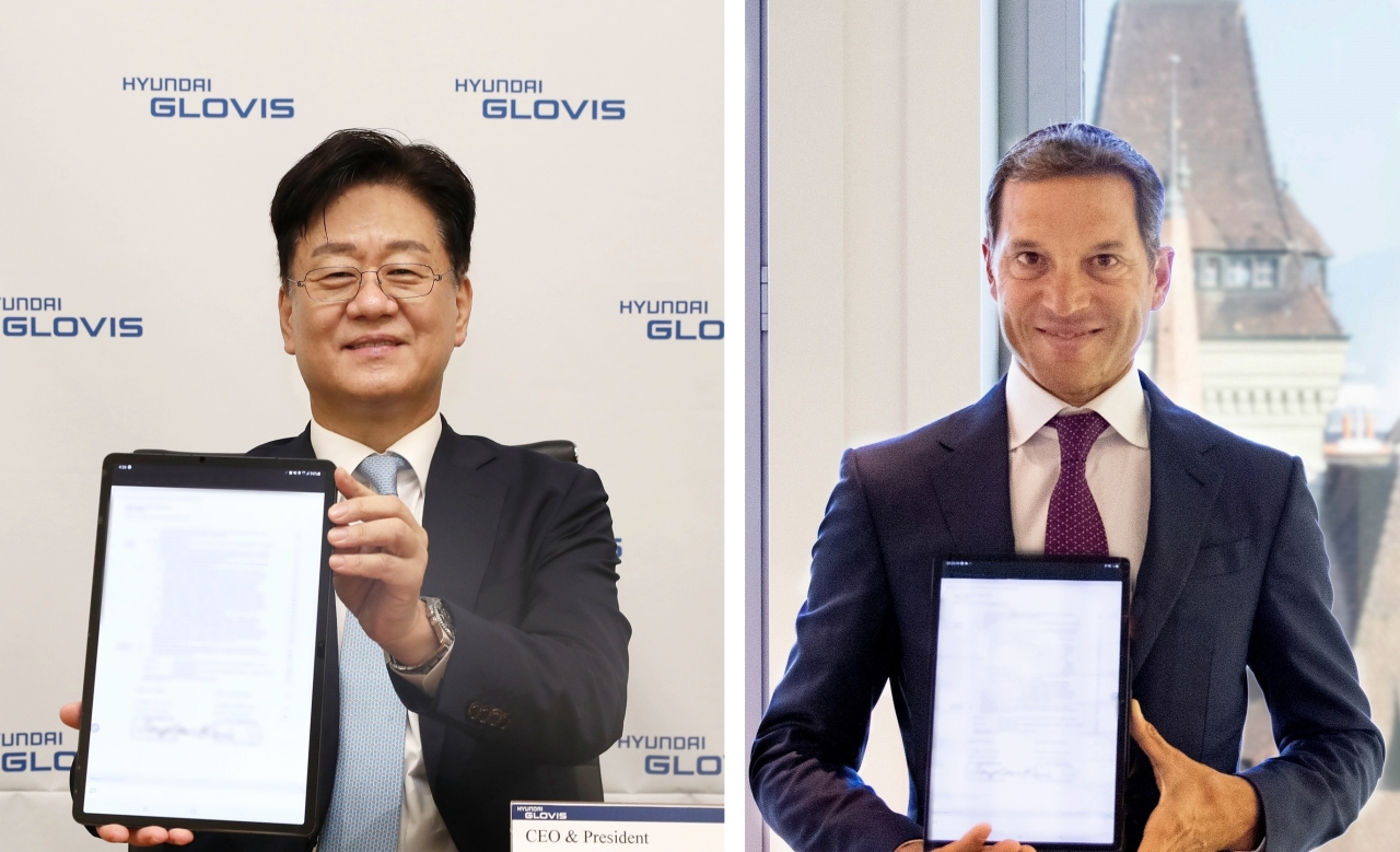Hyundai Glovis CEO Kim Jung-hoon (left) and Trafigura's executive director co-head of oil trading Jose Maria Larocca pose for photographs after they signed a business partnership deal in an online signing event held at their respective company headquarters in South Korea and Switzerland on Thursday. (Hyundai Glovis)