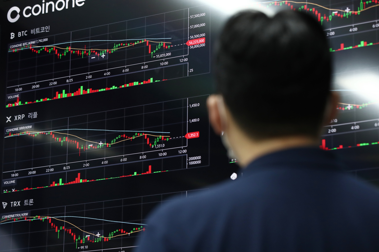 A man stares cryptocurrency prices on the display board at the Coinone customer center in Yongsan-gu, Seoul on Aug. 25. Coinone is one of major cryptocurrency operators in South Korea. (Yonhap)