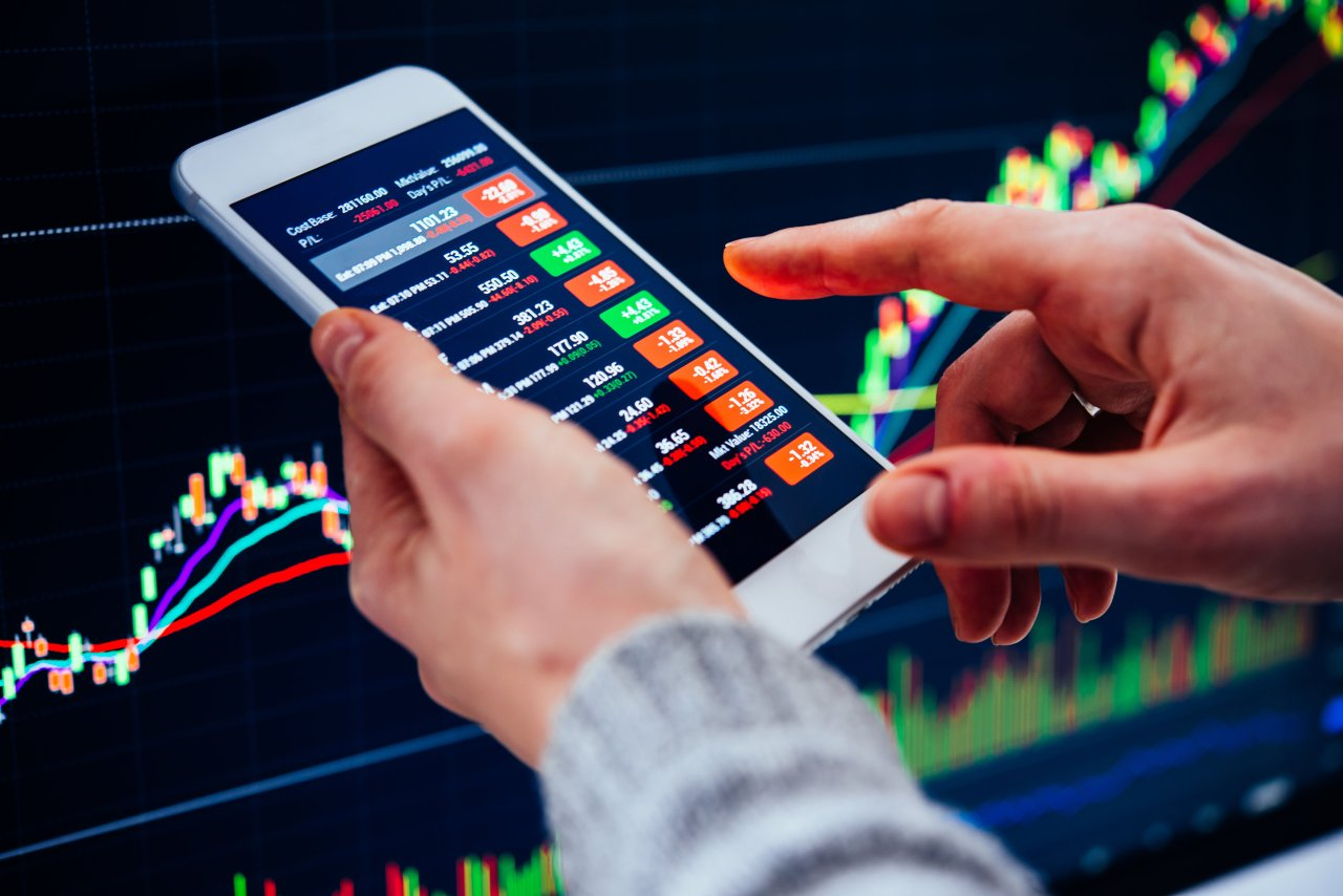 A day trader uses a smartphone for a stock investment. (123rf)
