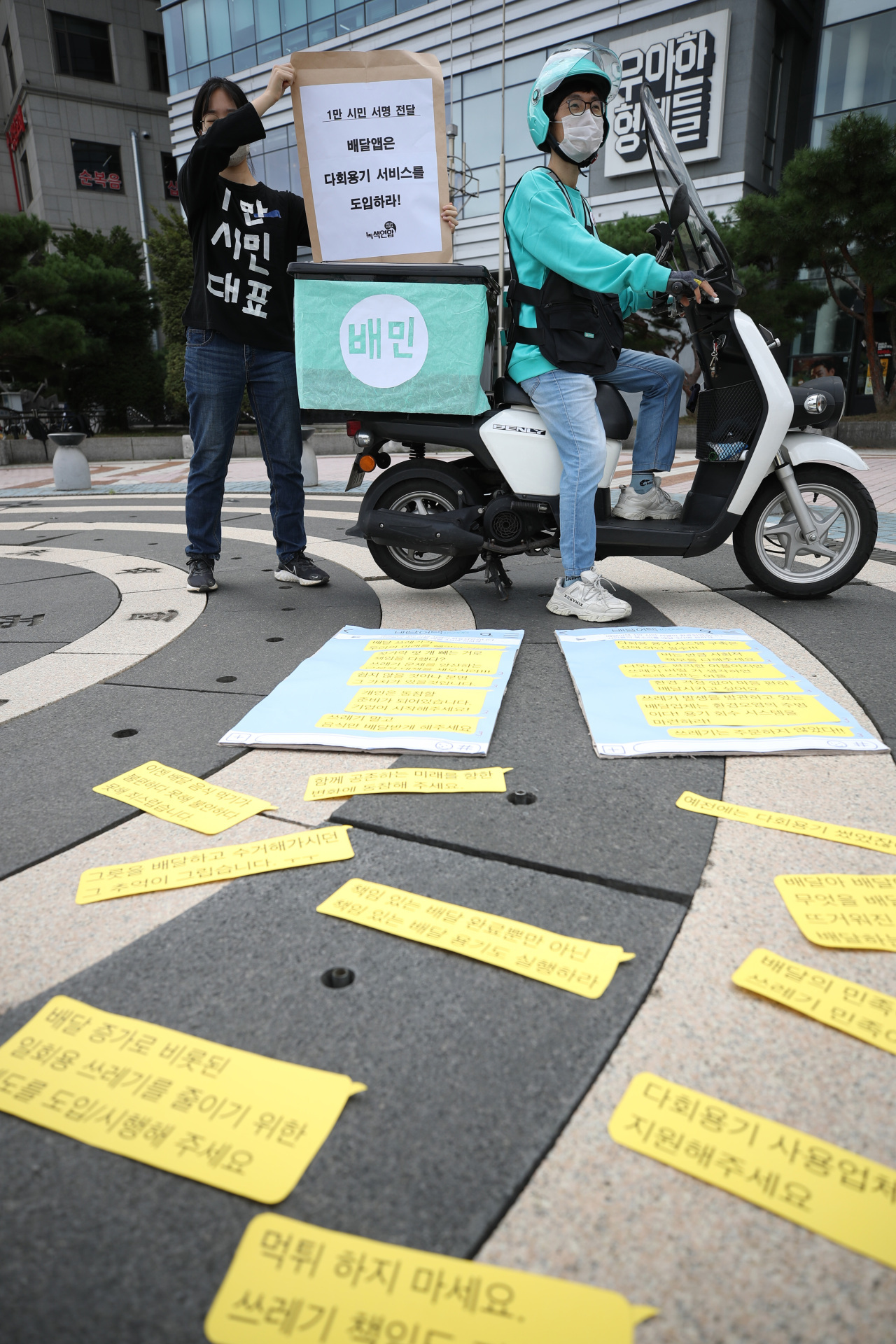Green Korea and Riders Union hold press conference to call on food delivery platforms to introduce the option of reusable containers in front of Baedal Minjok headquarters in Seoul on Thursday. (Yonhap)