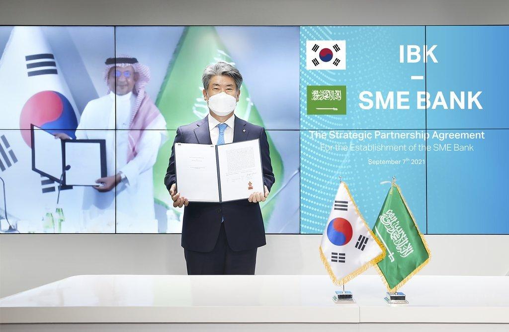 Industrial Bank of Korea CEO Yoon Jong-won and Saudi SME Bank Chairman Mohammad al-Tuwaijri pose for a photo Tuesday, in a videoconference held both in Seoul and Riyadh, Saudi Arabia. (IBK)